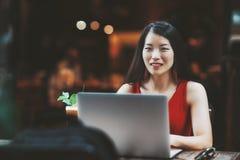 Portret van gelukkig Aziatisch meisje met laptop in straatbar stock fotografie