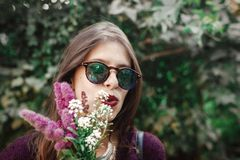 Portret van gelukkig bohomeisje die in zonnebril met boeket van wildflowers in zonnige tuin glimlachen Modieuze hipster onbezorgd royalty-vrije stock fotografie