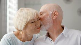 Portret van Gelukkig Hoger Paar thuis De hogere mens drukt zijn emoties uit en kust zijn vrouw royalty-vrije stock foto's