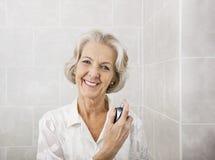 Portret van gelukkig hoger vrouwen bespuitend parfum in badkamers royalty-vrije stock afbeelding