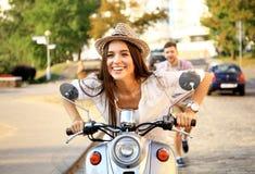 Portret van gelukkig jong paar die op autoped weg van reis genieten Stock Foto