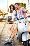 Portret van gelukkig jong paar die op autoped weg van reis genieten Stock Fotografie