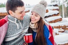 Portret van gelukkig jong paar die van picknick in sneeuw de winterpark genieten stock foto