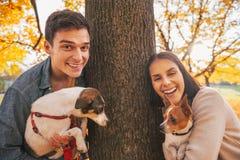 Portret van gelukkig jong paar met honden in openlucht in park Royalty-vrije Stock Afbeeldingen