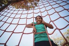 Portret van gelukkig meisje die een net beklimmen tijdens hinderniscursus royalty-vrije stock afbeeldingen