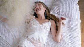 Portret van gelukkig meisje vrij van allergieën die op bed in sexy pyjama met boeket van veergrassen liggen stock videobeelden