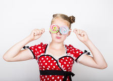 Portret van gelukkig mooi jong meisje met zoete candys de vrij jonge vrouw kleedde zich in een rode kleding met witte polka stock foto