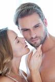 Portret van gelukkig mooi paar die en in wit omhelzen kussen Royalty-vrije Stock Afbeeldingen