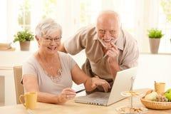 Portret van gelukkig oud paar dat online winkelt Stock Foto