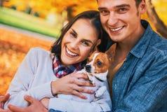 Portret van gelukkig paar met hond in openlucht in de herfst Royalty-vrije Stock Foto's