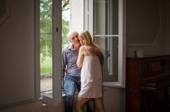 Portret van Gelukkig Paar met Leeftijdsverschil die zich dichtbij het Venster in Hun Huis tijdens de Zomer Hete Dag bevinden Psyc stock foto's