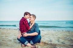 Portret van gelukkig paar op het strand Jonge man en vrouwenzitting op zandige kust en het koesteren Concept minnaars gelukkige o Royalty-vrije Stock Fotografie