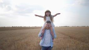 Portret van gelukkig vaderschap, jonge vrolijke vaderlooppas met zijn kleine leuke dochter op schouders die haar schudt stock video