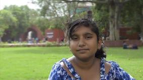 Portret van gelukkig vrolijk glimlachend tienermeisje die openlucht camerazitting bekijken op park bokeh achtergrond stock video