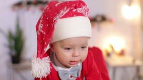Portret van gelukkig weinig baby in de hoeden van santa Het mirakel van Kerstmis stock videobeelden
