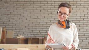 Portret van gelukkige aantrekkelijke vrouwelijke werknemer in glazen met pen en tablet in workshop stock video