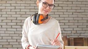 Portret van gelukkige aantrekkelijke vrouwelijke werknemer met pen en tablet in workshop Concept kleine onderneming stock footage