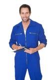 Portret van gelukkige automechanic het schrijven nota's stock foto