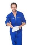 Portret van gelukkige automechanic het schrijven rekening stock afbeelding