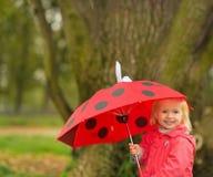 Portret van gelukkige baby met rode paraplu in openlucht royalty-vrije stock fotografie