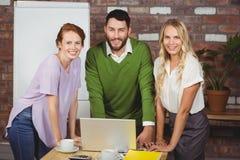 Portret van gelukkige bedrijfsmensen die op bureau leunen stock afbeeldingen