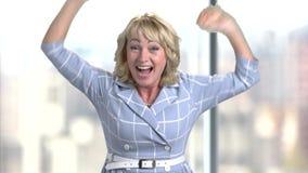 Portret van gelukkige bedrijfsvrouw op middelbare leeftijd in bureau verheugend succes stock videobeelden