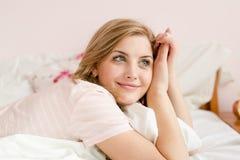 Portret van gelukkige blauwe ogen jonge blonde dame die pret het ontspannen in bed met bloemen in hand hoofdkussen en het gelukki royalty-vrije stock foto's
