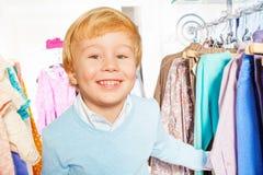 Portret van gelukkige blonde jongen status dichtbij hangers Stock Fotografie