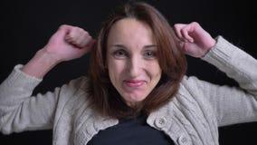 Portret van gelukkige donkerbruine Kaukasische vrouw die op middelbare leeftijd positief vermaak toont in camera op zwarte achter stock video