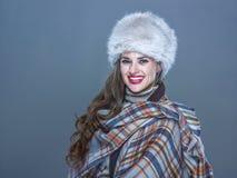 Portret van gelukkige elegante die vrouw in bonthoed op koud blauw wordt geïsoleerd stock foto