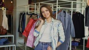 Portret van gelukkige en aantrekkelijke meisje status in kledingswinkel met kleurrijke zakken, het glimlachen graag en het bekijk stock videobeelden