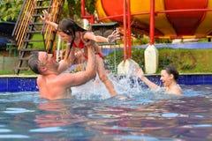Portret van gelukkige familie die pret in zwembad in de zomer hebben royalty-vrije stock afbeeldingen