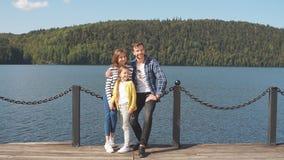 Portret van gelukkige familie: moeder, vader en kind in openlucht De mooie sportieve familie besteedt de dalingsvakantie aan aard stock videobeelden