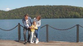 Portret van gelukkige familie: moeder, vader en kind in openlucht De mooie sportieve familie besteedt de dalingsvakantie aan aard stock footage