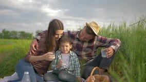 Portret van gelukkige familie, mum met papa en weinig jongen met koppen van melk in en handen die terwijl het ontspannen bij koes stock videobeelden