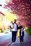 Portret van gelukkige familie op de gang langs de bloeiende de lentestraat royalty-vrije stock fotografie