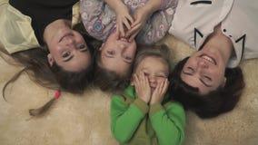 Portret van gelukkige familie van vier mensen die op pluizig tapijt op de vloer leggen, het glimlachen De vakantie van de pretfam stock video