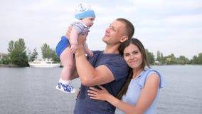 Portret van gelukkige familierecreatie op rivier, de zomerrest van gelukkig paar met baby op meer, stock videobeelden