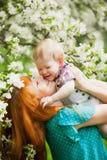 Portret van gelukkige gelukkige moeder en zoon in de lentetuin royalty-vrije stock foto's