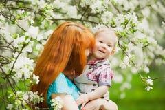 Portret van gelukkige gelukkige moeder en zoon in de lentetuin royalty-vrije stock afbeelding