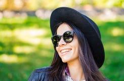 Portret van gelukkige gemengde ras jonge vrouw in hoed Spaans hipstermeisje in het park Dame die plaidoverhemd dragen en royalty-vrije stock foto
