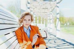 Portret van gelukkige glimlachende bedrijfsvrouw of manierstudente die met zonnebril op de bank in park zitten openlucht Stock Foto