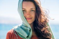 Portret van gelukkige glimlachende jonge vrouw met lang haar en groene sjaal op de strand en overzeese achtergrond stock afbeeldingen