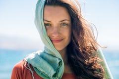 Portret van gelukkige glimlachende jonge vrouw met lang haar en groene sjaal op de strand en overzeese achtergrond Royalty-vrije Stock Afbeeldingen
