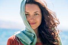 Portret van gelukkige glimlachende jonge vrouw met lang haar en groene sjaal op de strand en overzeese achtergrond royalty-vrije stock foto