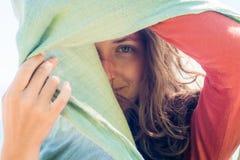 Portret van gelukkige glimlachende jonge vrouw met lang haar Zij verbergt en creeert een schaduw met sjaal stock afbeeldingen
