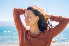Portret van gelukkige glimlachende jonge vrouw op strand en overzeese achtergrond De windspelen met meisje snakken haar Stock Afbeeldingen
