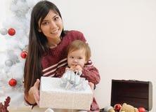 Portret van gelukkige glimlachende moeder en haar baby dichtbij Kerstmis tre Royalty-vrije Stock Foto's