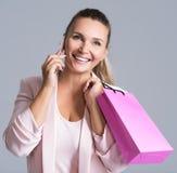 Portret van gelukkige glimlachende vrouw met roze zak die spreekt stock fotografie