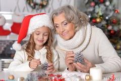 Portret van gelukkige grootmoeder en haar weinig kleindochter die voor Kerstmis samen thuis voorbereidingen treffen royalty-vrije stock foto's